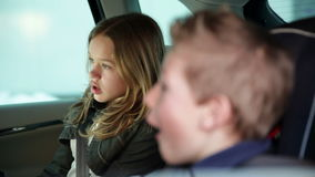 Playful kids in the back of the car while family driving to vacation stock video footage