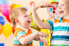 Playful kids boys with clown on birthday party. Joyful kids with clown on birthday party Royalty Free Stock Photos