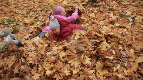 Playful kids lying in pile of yellow foliage. Two smiling siblings lying on their bellies in a pile of fallen autumn leaves, throwing them up in the air in stock footage