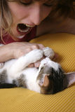 Playful kitten 1. Young girl with her playful kitten stock image