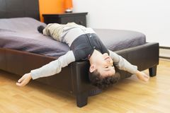 Playful little boy in bed upside down Stock Photos