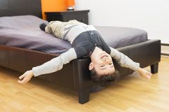 Playful little boy in bed upside down Royalty Free Stock Image