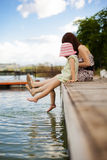 Playful little family. Young mother and her daughter splashing in the lake Royalty Free Stock Image
