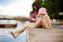 Playful little family. Young mother and her daughter sitting on a pier Stock Image