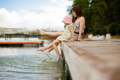 Playful little family. Young mother and her daughter splashing in the lake Stock Images