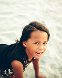 Playful little girl on the beach scrolling on the sand Stock Images
