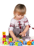 Playful little girl in embroided blouse. A cheerful little girl dressed in embroidered shirt is playing blocks; isolated on the white background Royalty Free Stock Photo