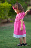 Playful little girl in the park. Playful little girl in the park, she is ready to play and looking curiously to someone Royalty Free Stock Photography