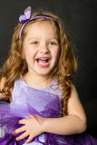 Playful little girl in purple dress laughing Royalty Free Stock Images
