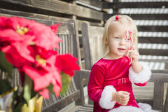 Playful Little Girl Sitting On Bench with Her Candy Cane Royalty Free Stock Image