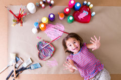Playful little girl surrounded by her paints Royalty Free Stock Photo