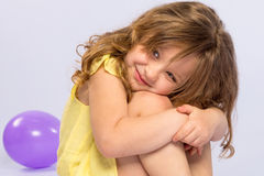Playful little girl in yellow dress smiling Royalty Free Stock Photography