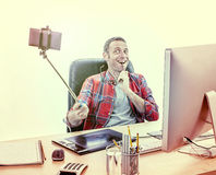 Playful male graphic designer taking a dynamic business selfie. Playful male graphic designer at his computer enjoying taking a dynamic selfie biting his Royalty Free Stock Photography
