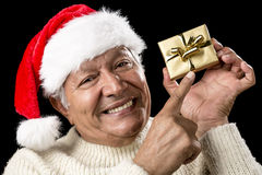 Playful Male Pensioner Pointing At Golden Gift. Coquettish elderly man wearing a red Santa Claus cap and a warm, white pullover. He is pointing his right index Royalty Free Stock Photos
