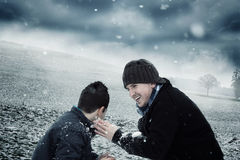Playful man and boy playing with snow outside Royalty Free Stock Photo