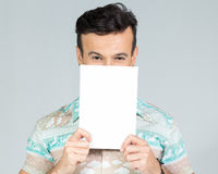 Playful man covers half the face with a blank rectangular cartel. Man smiles and plays with the banner for advertising content. Handsome brazilian male wearing a Royalty Free Stock Photography