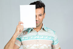 Playful man covers half the face with a blank rectangular cartel. Man smiles and plays with the banner for advertising content. Handsome brazilian male wearing a Royalty Free Stock Photos