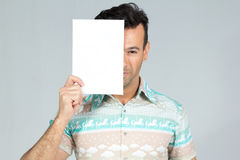 Playful man covers half the face with a blank rectangular cartel. Man smiles and plays with the banner for advertising content. Handsome brazilian male wearing a Stock Image