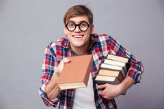 Playful man in funny round glasses giving youn a book Stock Images