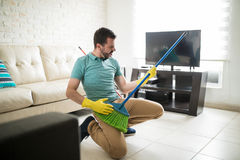 Attractive man using broom as a guitar. Playful man in the living room having fun while doing house chores and holding a broom as a guitar Stock Photography