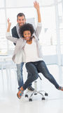 Playful man pushing woman on chair in office Royalty Free Stock Image