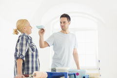 Playful man putting paint on woman's nose in new house Stock Photo