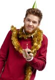 Playful man with tinsel holds small tart Stock Photography