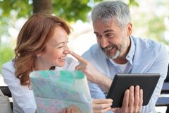 Playful mature tourists sitting on a bench, working on a tablet and looking at the city map royalty free stock image