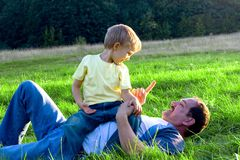 Playful In The Meadow 2. Father and son sharing a playful moment in a green meadow Royalty Free Stock Photos