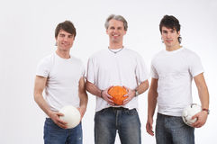 Playful men. Three men in a row holding three balls