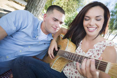 Playful Mieced Race Couple at the Park Playing Guitar and Singing Stock Image