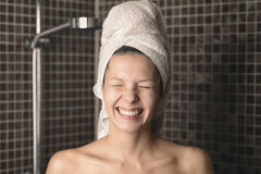 Playful mischievous woman with wet hair in a towel. Playful mischievous naked woman with her wet hair in a towel giving the camera a big cheesy grin with her stock image