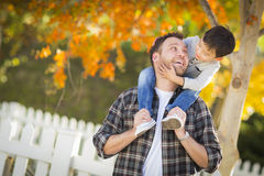Playful Mixed Race Boy Having Fun on Shoulders of Caucasian Father Stock Image