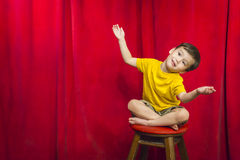 Playful Mixed Race Boy Sitting on Stool in Front of Curtain Royalty Free Stock Photos