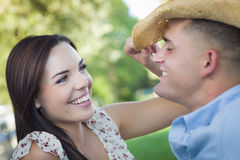 Playful Mixed Race Couple with Cowboy Hat Flirting in Park Royalty Free Stock Photos