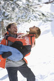 Playful mixed race couple in snow, man carrying woman royalty free stock photography