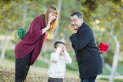 Playful Mixedrace Parents With Gifts for Young Boy Hiding Eyes Stock Image