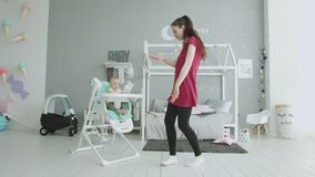 Playful mom entertaining baby sitting in highchair stock video footage