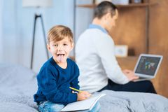 Little boy showing his tongue while drawing. Playful mood. Cute little boy sitting on the bed, drawing and showing his tongue while his father working on the Royalty Free Stock Photo