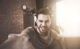 Optimistic young bearded man is making photo stock images