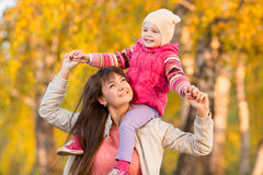 Playful mother with child girl walking outdoors in autumnal park Stock Photos