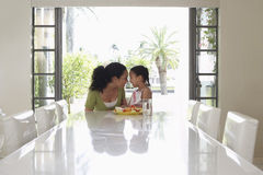 Playful Mother And Daughter At Dining Table Stock Photography