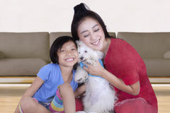 Playful mother and her daughter with dog Royalty Free Stock Image