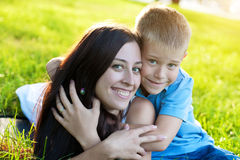 Playful Mother and son siting on grass Royalty Free Stock Image