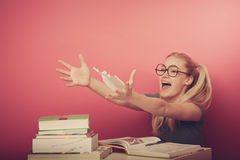 Playful, naughty schoolgirl with big eyeglasses playing with pap Stock Image