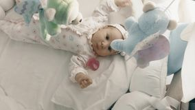 Playful newborn baby girl in her cot Royalty Free Stock Image