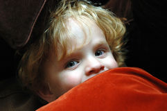 Playful peeking toddler. A cute blond toddler peeking out from a pile of pillows stock image