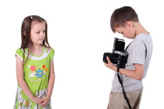 Playful photo-session. Children play: the boy photographs the girl Royalty Free Stock Photos