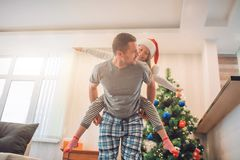 Playful picture of happy father and daughter spending time together. He rides her on his back. They are happy. stock image