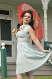 Playful pin up girl with a red parasol Stock Photos